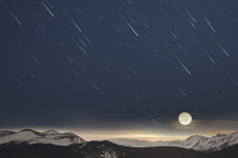 The crescent moon sets over snowy mountains as star trails streak toward the horizon.