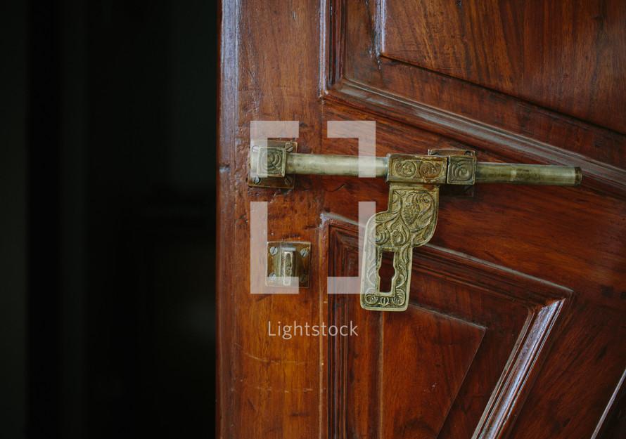 a brass latch on a wooden door