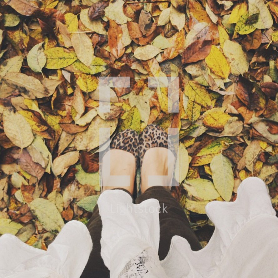 Feet in leopard fabric shoes standing in fall leaves.