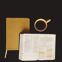 Two Bibles and a cup of coffee against a black background.