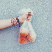 a hand holding a bag of peaches