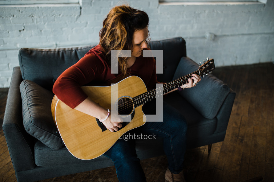 a woman sitting on a couch playing a guitar
