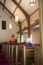 an elderly woman sitting alone in a church praying