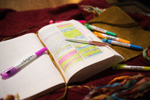 highlighters and pens on an open Bible
