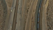 aerial view over a train on the tracks and traffic on a highway