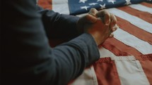 Person praying with folded hands over the American flag.