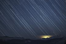 Star trails streak across the night sky toward the snowy mountains on the horizon.