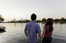 couple holding hands in front of a lake