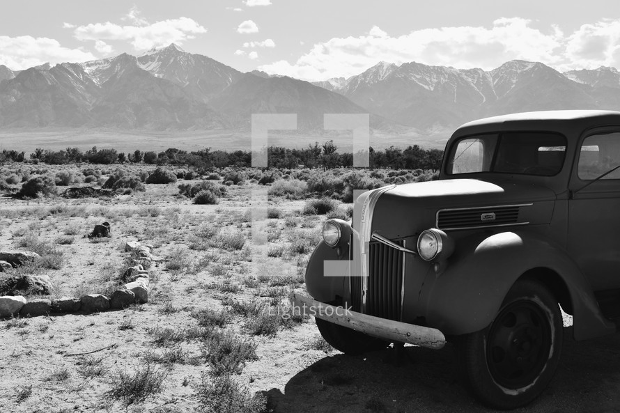 vintage car parked in front of mountains