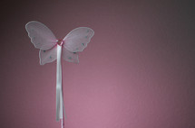 Pink decorative butterfly wand with heart shaped jewel head and ribbons.