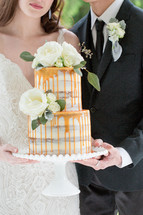 bride and groom holding a wedding cake