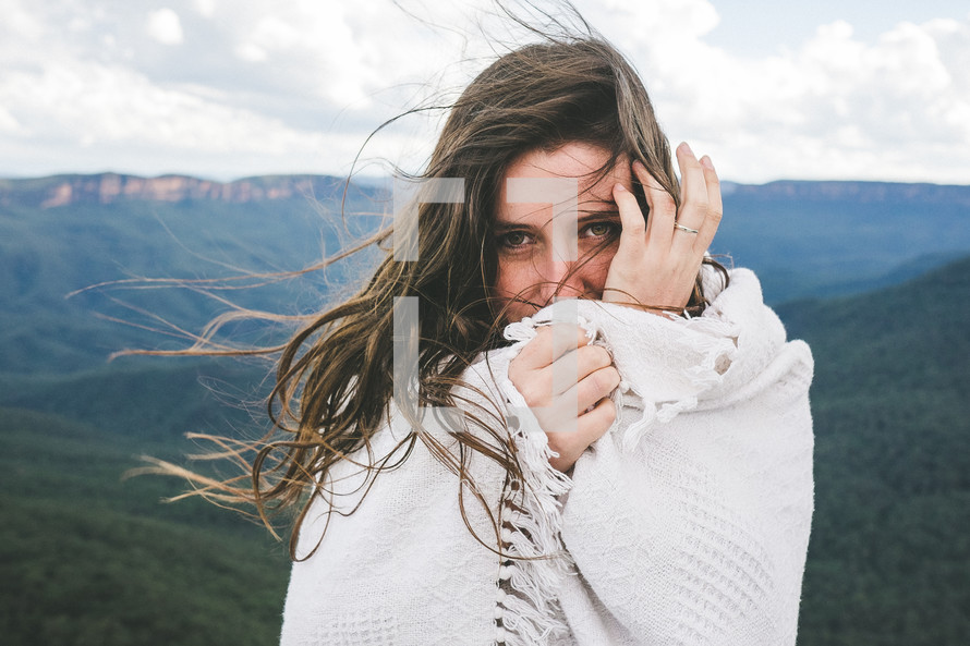 woman wrapped in a blanket standing on a mountain top