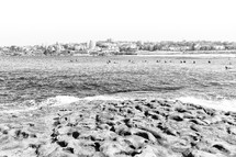 surfers in a bay and rocky shore
