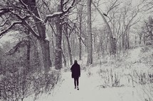 a woman walking through a winter forest in snow