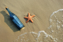sea star and bottle on a beach
