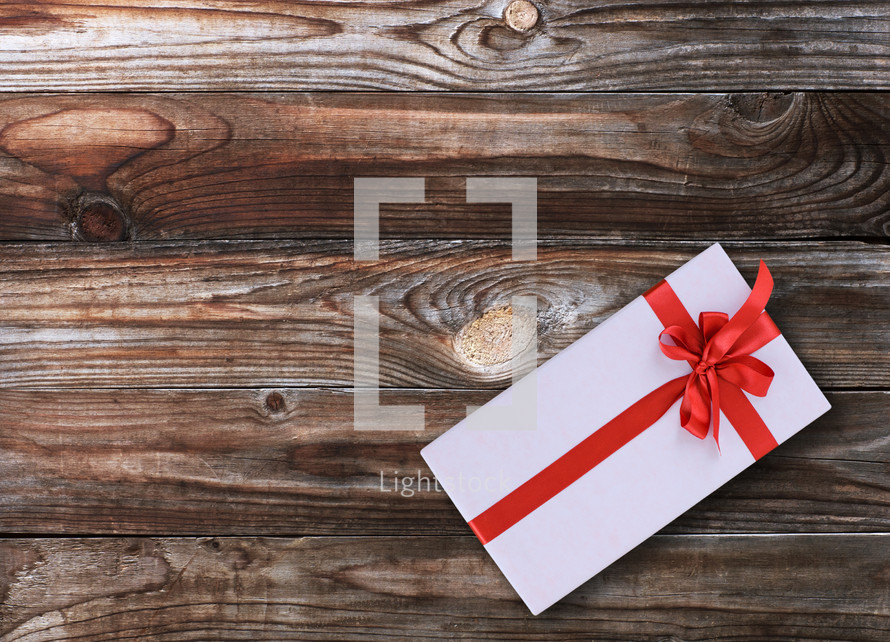 Wrapped gift box with a bow on a wooden floor,