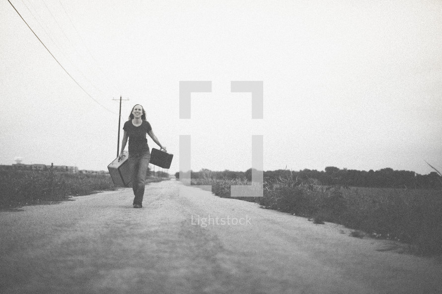woman walking down a road carrying suitcases
