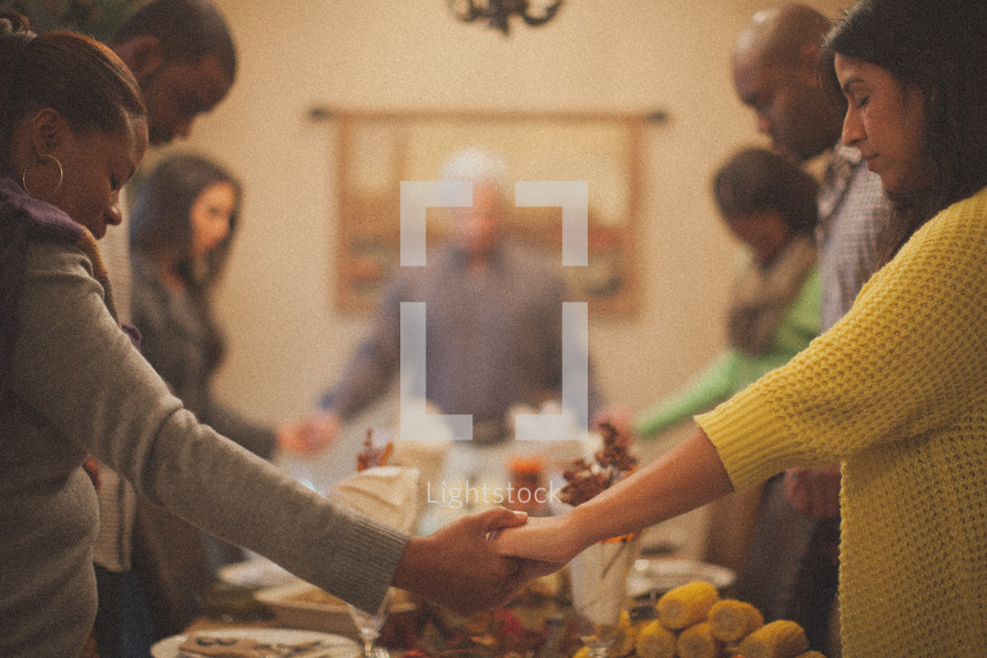 holding hands in prayer around a Thanksgiving dinner table