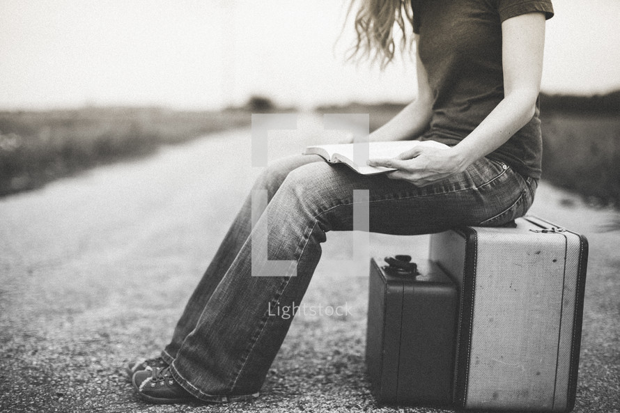 Woman sitting on a suitcase in the middle of the road with an open Bible in her lap.