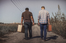 men walking down a dirt road with suitcases