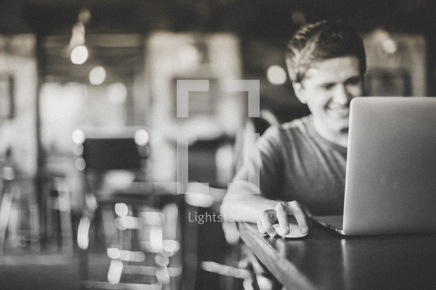 man working at his laptop in a cafe