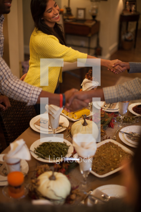 shaking hands in greeting and welcome at a Thanksgiving dinner table