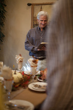 Man reading a Bible verse in prayer at a Thanksgiving table