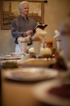 man reading a Bible at a Thanksgiving dinner table