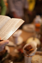 man reading the Bible in prayer at a Thanksgiving dinner