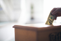 hand placing a dollar in a tithe box