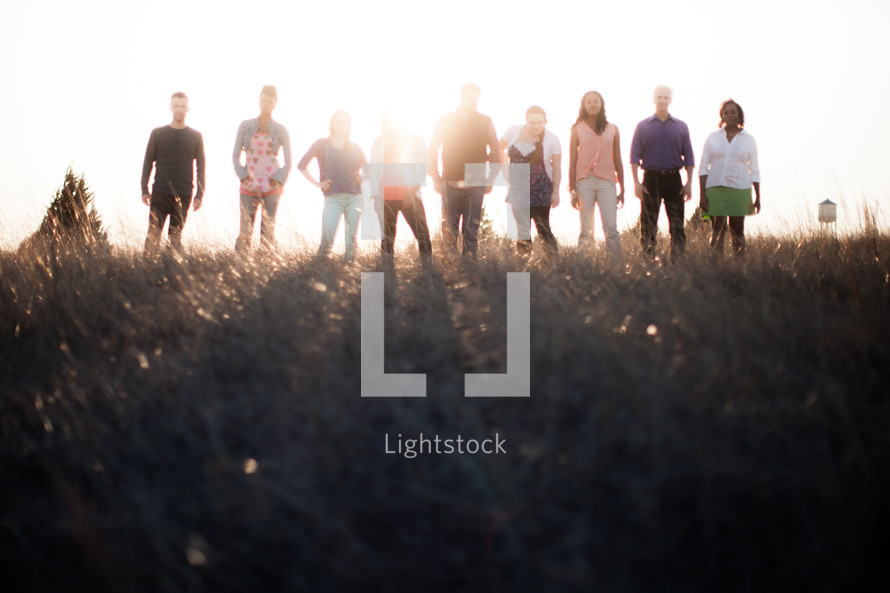 group of people in a row standing outdoors in sunlight