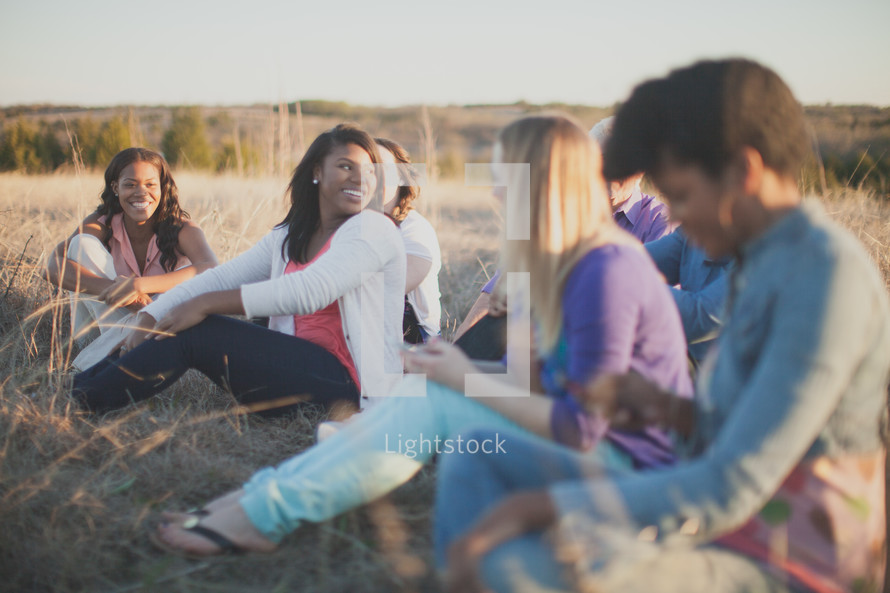 women sitting in the tall grass outdoors