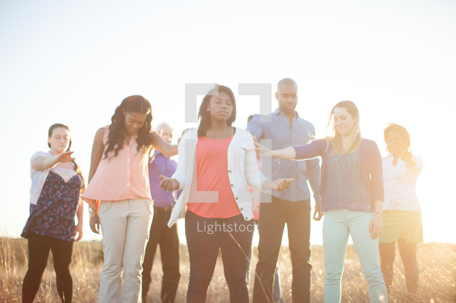 hands on a women in prayer outdoors