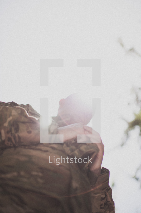 soldier holding his hat and praying