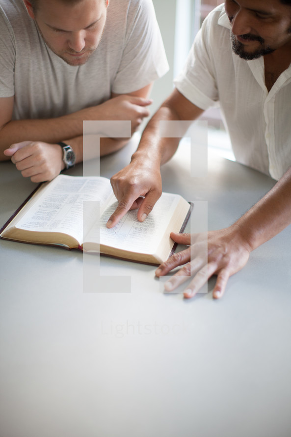 Two men at a table studying a Bible.