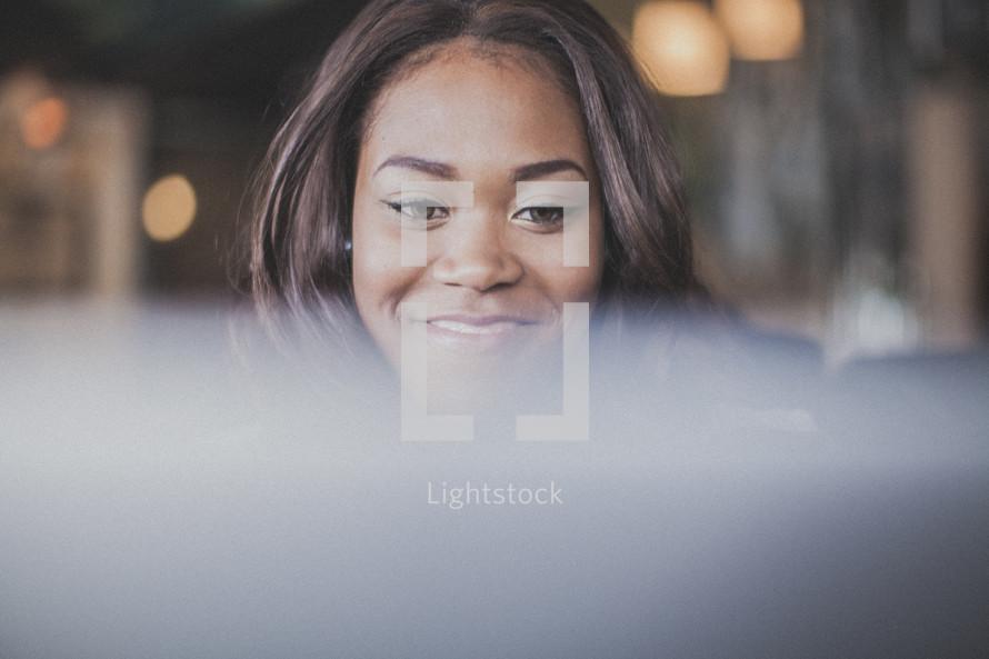 woman smiling looking at a computer screen
