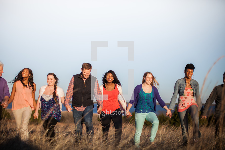 group of people holding hands walking through a field