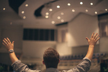 man standing in an empty church with his hands raised in worship to God