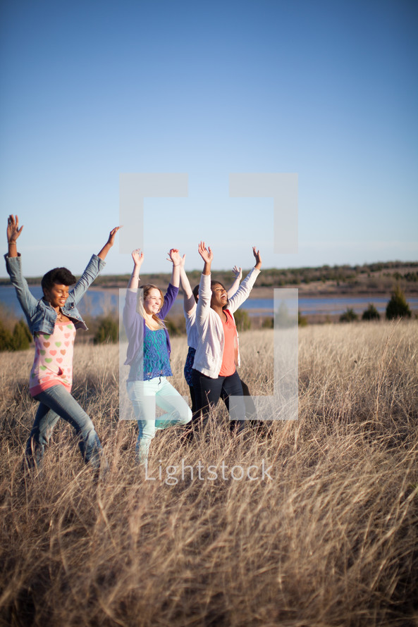 women walking through a field of tall grasses with their hands raised