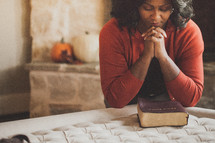 Woman praying over a Bible on the corner of her bed.