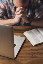 man with his head bowed in prayer by a laptop and Bible