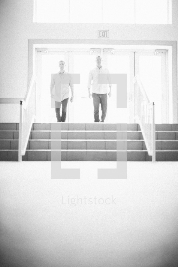 Two men entering a building through sunlit, illuminated doorway.
