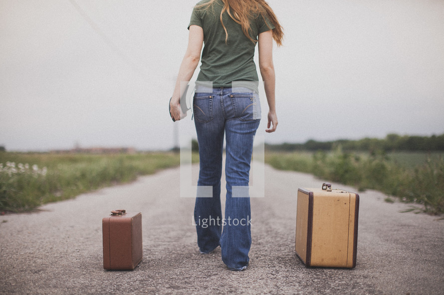 Woman with Bible walking in the middle of a dirt road with suitcases.