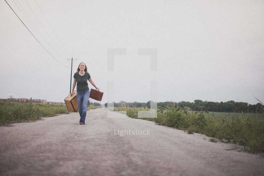 Woman walking down the middle of a dirt road holding suitcases.