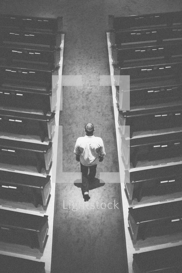 man walking down the aisle of a church