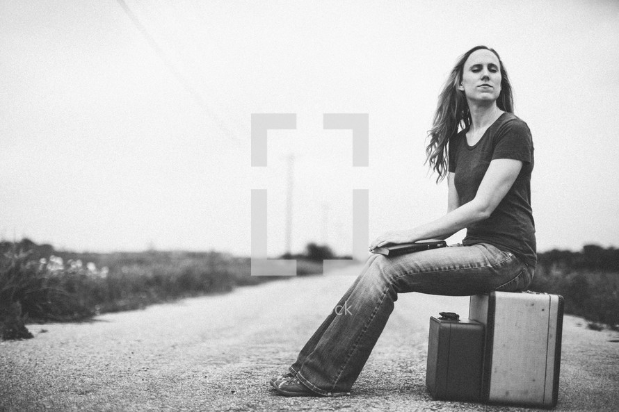 woman sitting on a suitcase in the middle of a road holding a Bible
