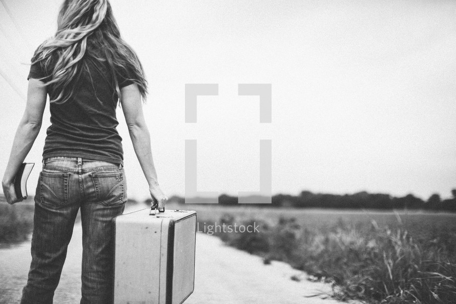woman carrying a suitcase looking down a long road