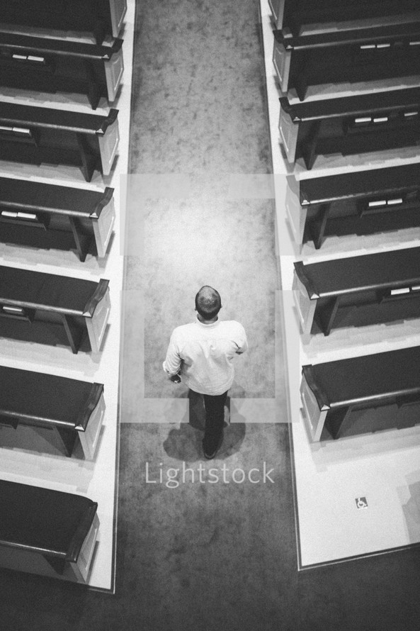man walking down the aisle of a church