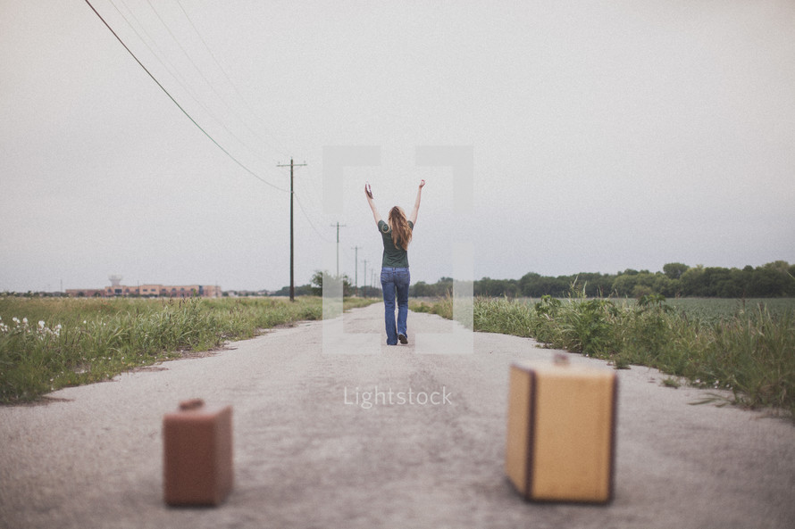 Woman with arms raised walking in the middle of the road, away from suitcases.