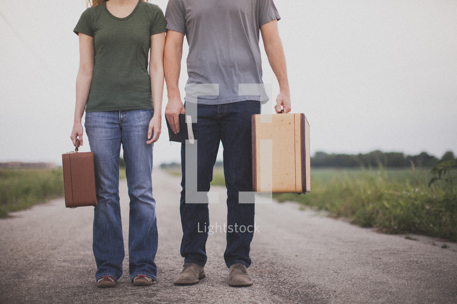 Couple with suitcases and a Bible standing in the middle of a dirt road.